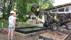 """Emily Dixon (left) and Graham Coffman stand by as Marcin Jakubowski dumps soil into the raised garden beds using the OSE tractor, """"LifeTrac."""""""